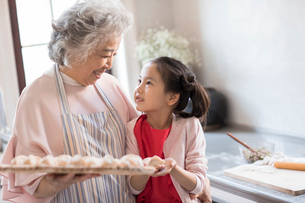 Cheerful Chinese granddaughter and grandmother making dumplings in kitchenの写真素材 [FYI02227454]