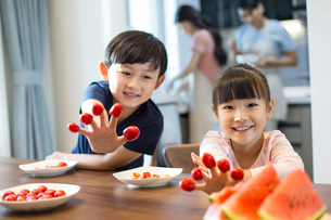 Happy siblings and cherry tomatoesの写真素材 [FYI02227488]