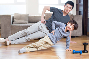 Young father and son exercising at homeの写真素材 [FYI02227506]