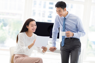Confident Chinese business people talking in officeの写真素材 [FYI02227523]