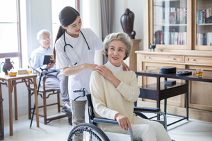 Nursing assistant taking care of senior woman in wheel chairの写真素材 [FYI02227530]