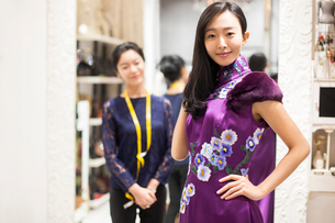 Chinese fashion designer examining dress on customerの写真素材 [FYI02227534]