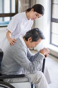 Nursing assistant taking care of senior man in wheel chairの写真素材 [FYI02227567]