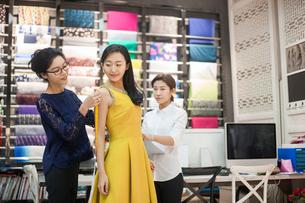Chinese fashion designers taking measurement of customerの写真素材 [FYI02227571]