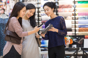 Chinese friends paying with smart phone in clothing storeの写真素材 [FYI02227572]