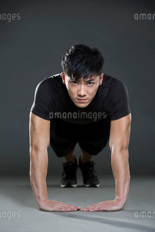 Young man doing push-upsの写真素材 [FYI02227609]