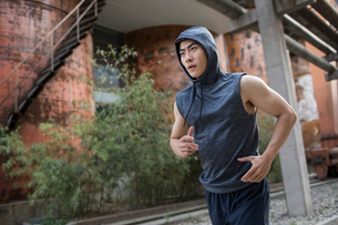 Young Chinese man jogging outdoorsの写真素材 [FYI02227623]