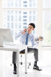 Young Chinese businessman exercising in officeの写真素材 [FYI02227625]