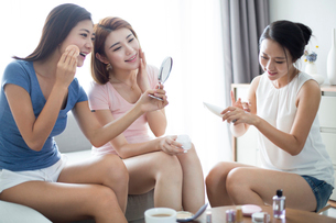 Best female friends applying make-up at homeの写真素材 [FYI02227628]