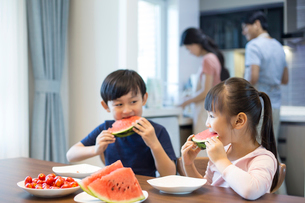 Happy siblings eating watermelonの写真素材 [FYI02227633]