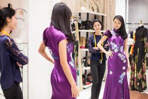 Chinese fashion designer examining dress on customerの写真素材 [FYI02227640]