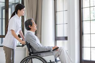 Nursing assistant taking care of senior man in wheel chairの写真素材 [FYI02227680]