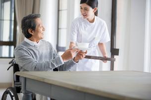 Nursing assistant taking care of senior man in wheel chairの写真素材 [FYI02227715]