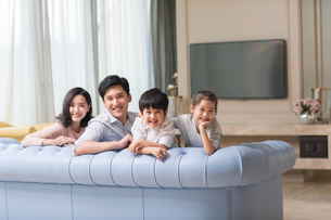 Portrait of cheerful young Chinese family in the living roomの写真素材 [FYI02227739]