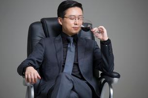 Mid adult businessman enjoying red wineの写真素材 [FYI02227748]