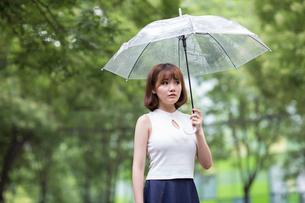 Sullen young woman holding umbrellaの写真素材 [FYI02227763]