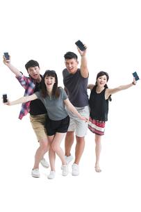 Young friends showing smart phonesの写真素材 [FYI02227785]