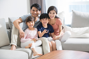 Happy young family watching TVの写真素材 [FYI02227819]