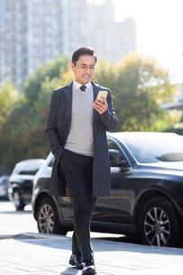 Confident Chinese businessman using smart phoneの写真素材 [FYI02227834]