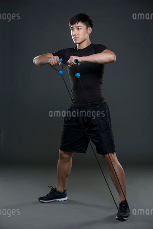 Young man exercising with resistance bandの写真素材 [FYI02227838]