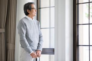 Senior man looking out windowの写真素材 [FYI02227848]