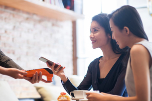 Chinese friends paying with smart phone in cafeの写真素材 [FYI02227855]