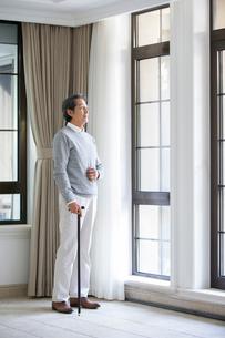 Senior man looking out windowの写真素材 [FYI02227862]