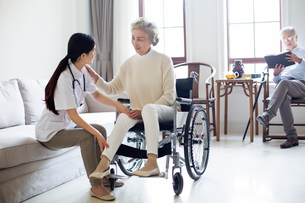 Nursing assistant taking care of senior woman in wheel chairの写真素材 [FYI02227887]