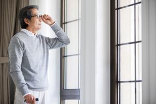 Senior man looking out windowの写真素材 [FYI02227914]