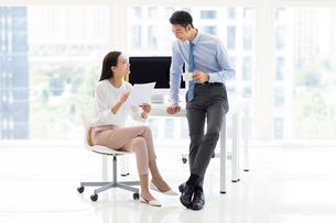 Confident Chinese business people talking in officeの写真素材 [FYI02227915]