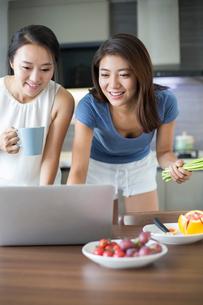 Best female friends using laptop for online recipeの写真素材 [FYI02227944]