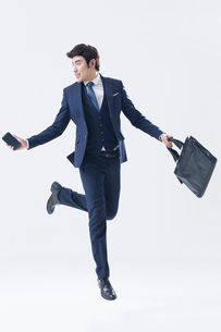 Young Chinese businessman running with briefcase and smart phoneの写真素材 [FYI02227945]