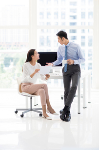 Confident Chinese business people talking in officeの写真素材 [FYI02227961]