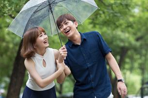 Young couple holding umbrellaの写真素材 [FYI02227964]