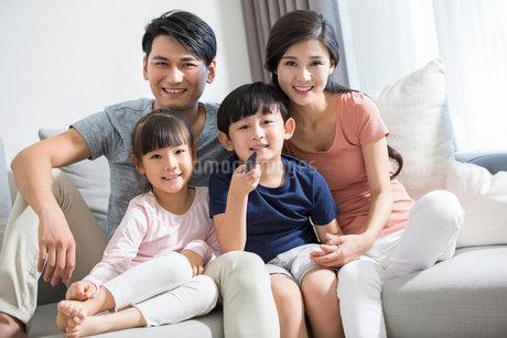 Happy young family watching TVの写真素材 [FYI02227971]