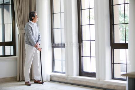Senior man looking out windowの写真素材 [FYI02227984]