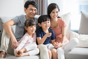 Happy young family watching TVの写真素材 [FYI02227997]