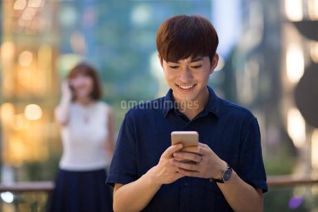 Happy young man using smart phoneの写真素材 [FYI02228004]