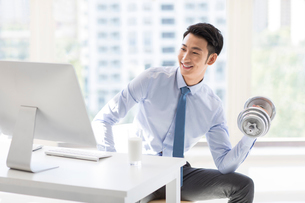 Young Chinese businessman exercising in officeの写真素材 [FYI02228007]