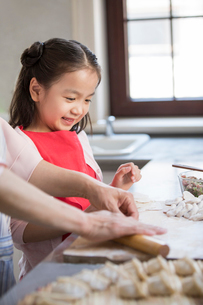 Cheerful Chinese granddaughter and grandmother making dumplings in kitchenの写真素材 [FYI02228009]