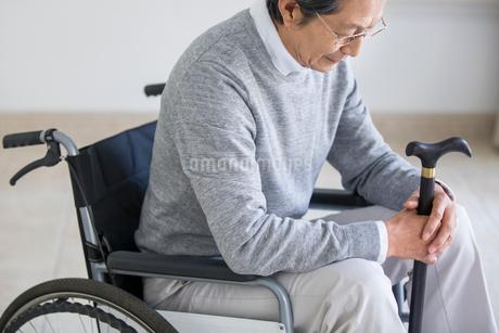 Senior man in wheelchair holding a caneの写真素材 [FYI02228011]