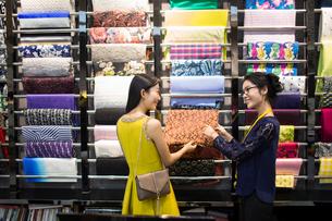 Chinese fashion designer helping customer choosing fabric swatchの写真素材 [FYI02228015]