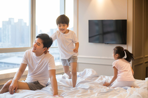 Cheerful young Chinese family having fun on a bedの写真素材 [FYI02228033]