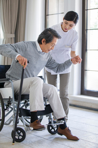 Nursing assistant taking care of senior man in wheel chairの写真素材 [FYI02228038]