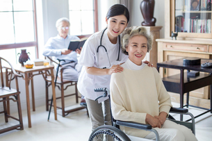 Nursing assistant taking care of senior woman in wheel chairの写真素材 [FYI02228046]