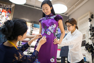 Chinese fashion designers adjusting customer's dressの写真素材 [FYI02228047]