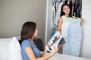 Young woman choosing dress from wardrobeの写真素材 [FYI02228070]