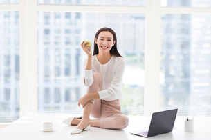Young Chinese businesswoman holding an apple in officeの写真素材 [FYI02228082]