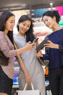 Chinese friends paying with smart phone in clothing storeの写真素材 [FYI02228089]