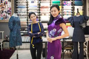 Chinese fashion designer examining dress on customerの写真素材 [FYI02228103]